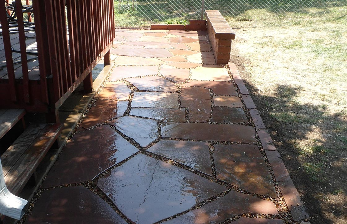 Red flagstone walkway with pea stone gravel