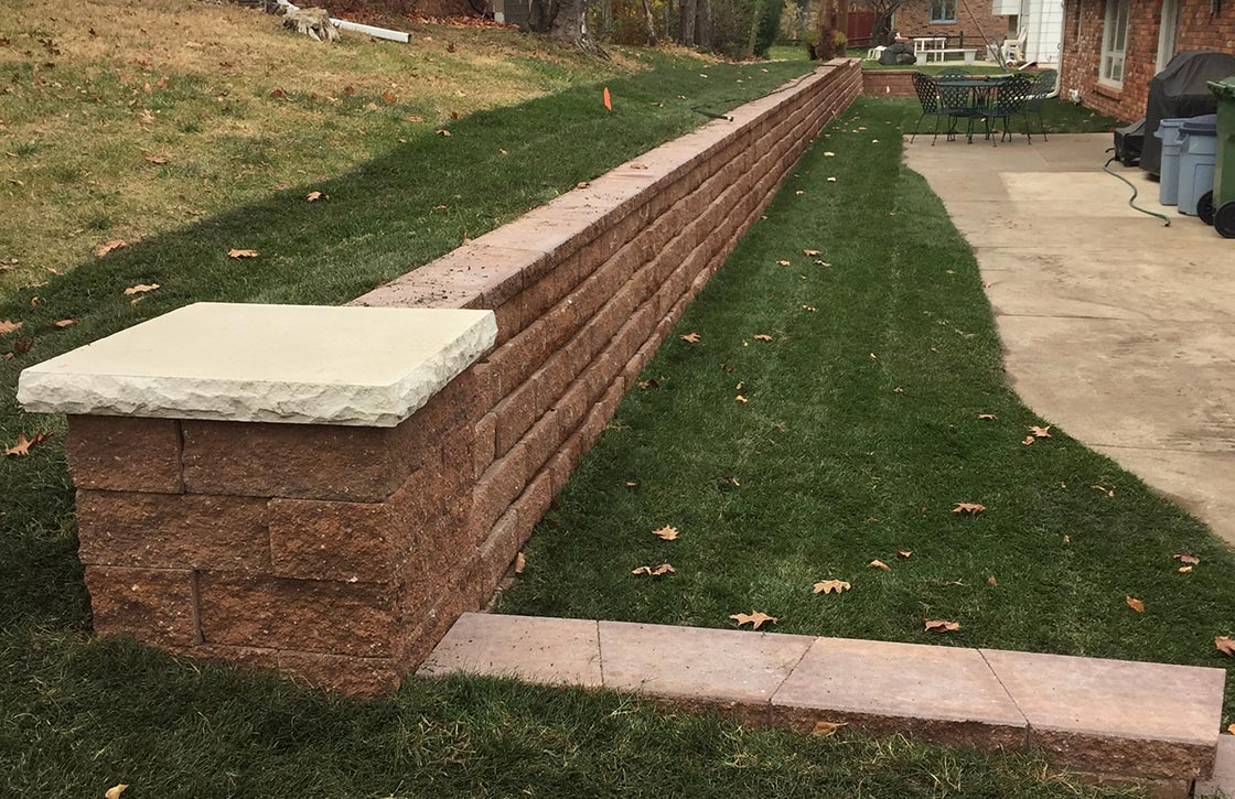 Natural stone retaining wall hardscape along property line