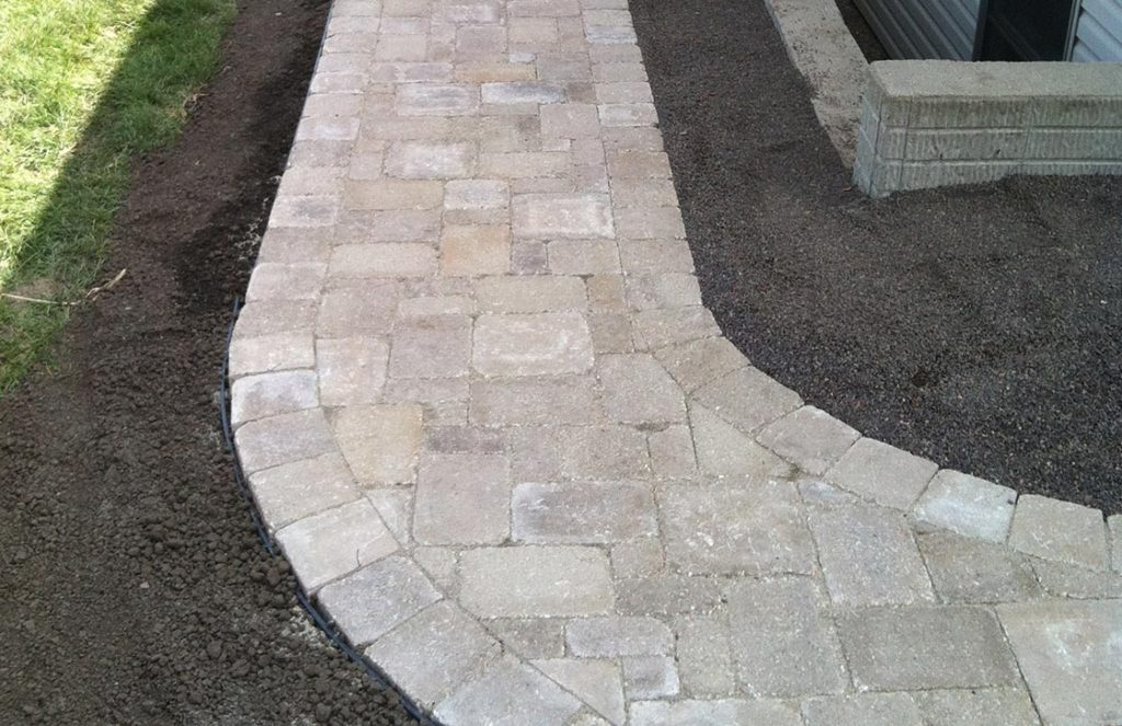 Curved walkway with grey and tan stone pavers