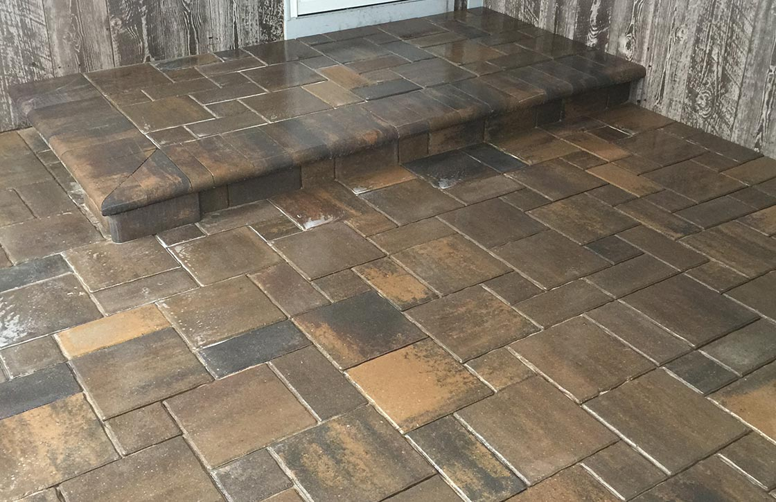 Patio with brown, travertine stone pavers and small step hardscape