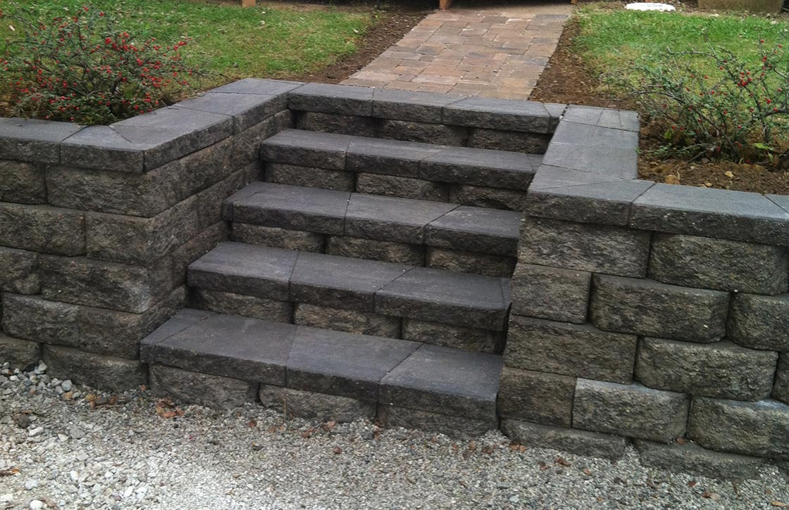 Dark grey, natural stone retaining wall with steps
