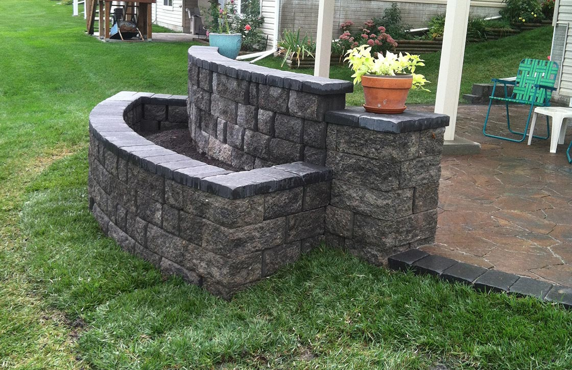 Natural stone, freestanding accent wall with raised flower bed hardscape on patio