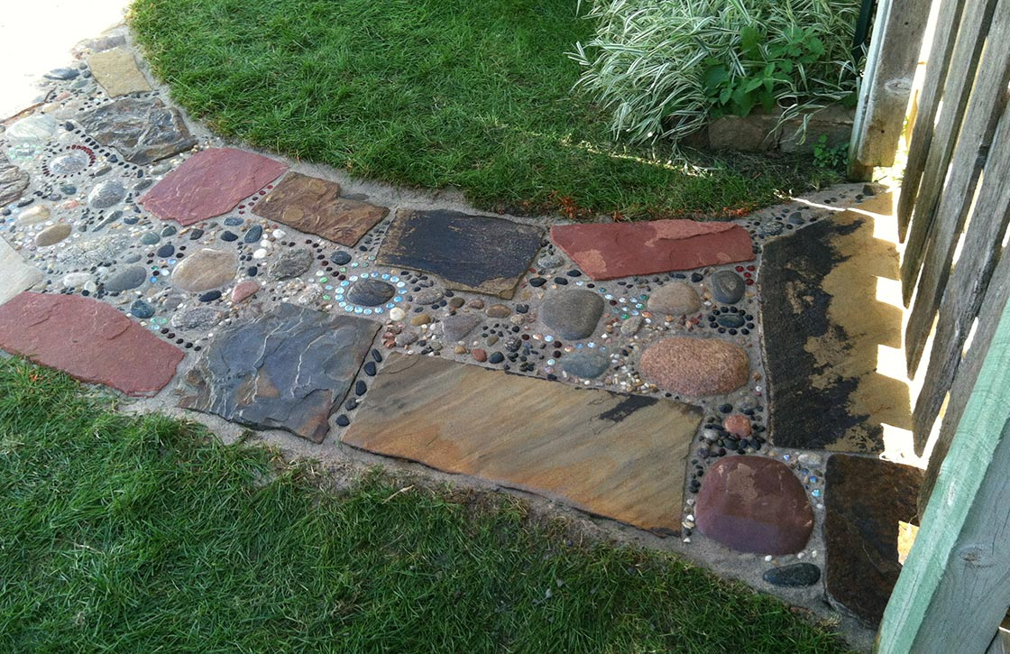 Custom stone walkway hardscape with decorative mural pattern