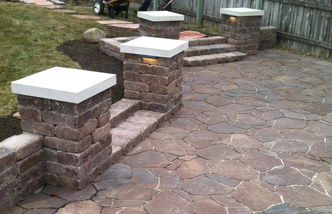 Custom patio with red flagstone pavers, stone steps, weathered stone retaining wall, columns and column cap