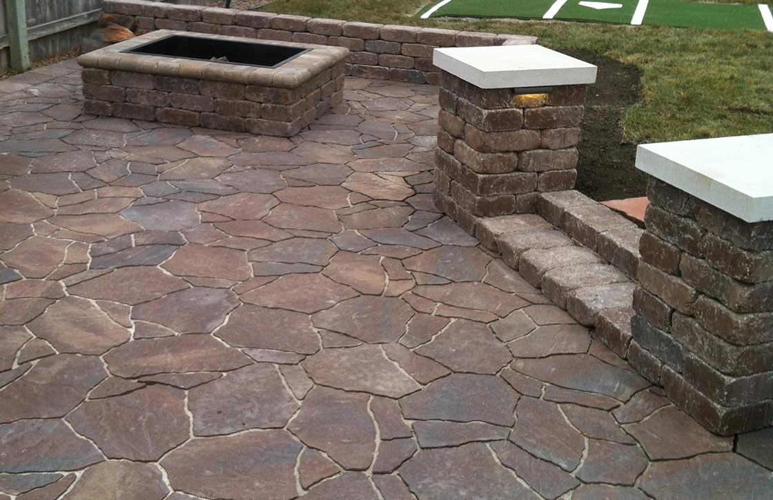 Custom patio with red flagstone pavers, square fire pit, stone step, and weathered stone retaining wall