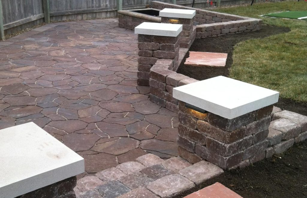 Custom patio with red flagstone pavers, square fire pit, weathered stone retaining wall, freestanding stone column, and column cap