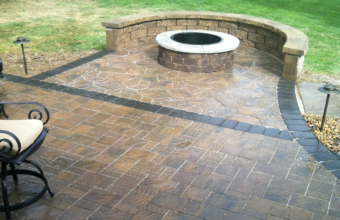 Round, above ground stone fire pit with freestanding stone wall on patio with flagstone pavers