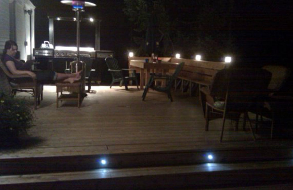 Large, wooden deck with built in seating area and custom, built in lighting