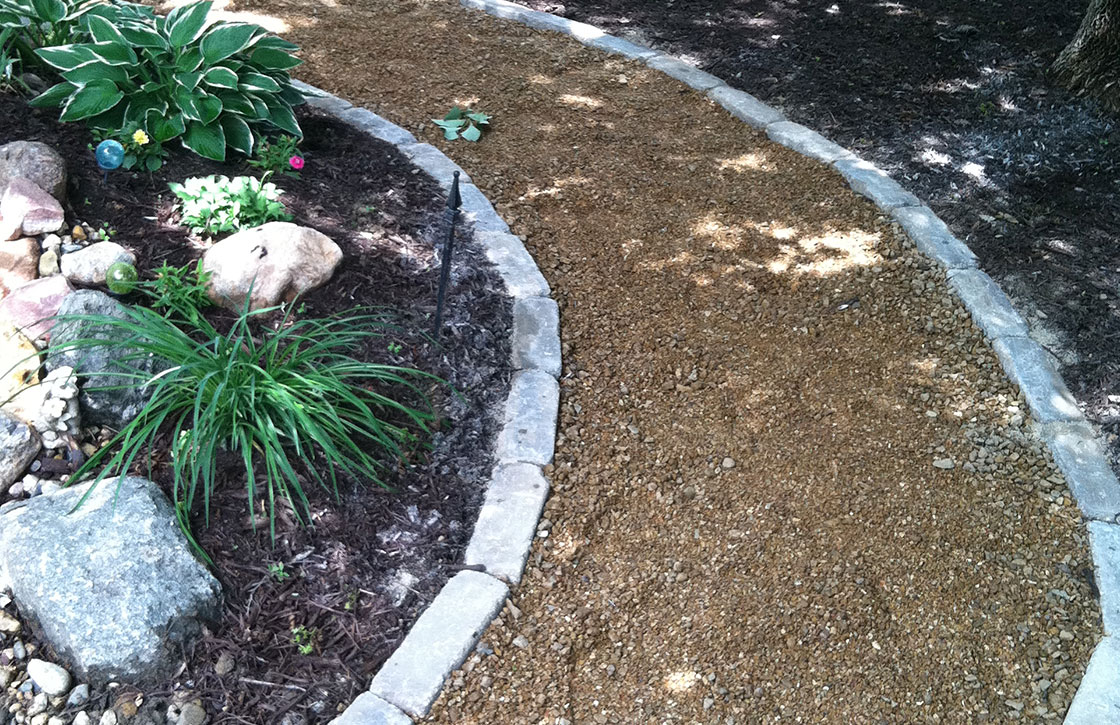 Curved, gravel garden walkway with cement brick edging