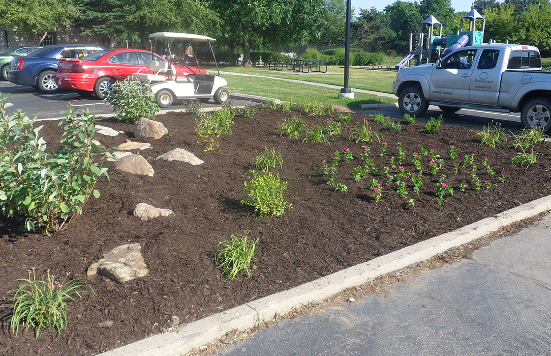 Commercial landscape of raised mulched flower bed with various small bushes, flowers, and decorative rocks