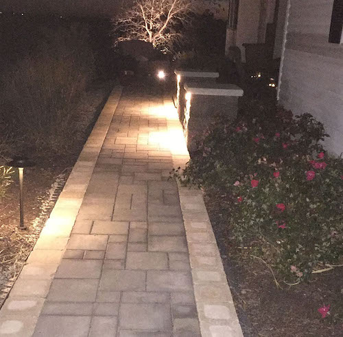 Walkway with concrete pavers, stone pillars, and custom lighting