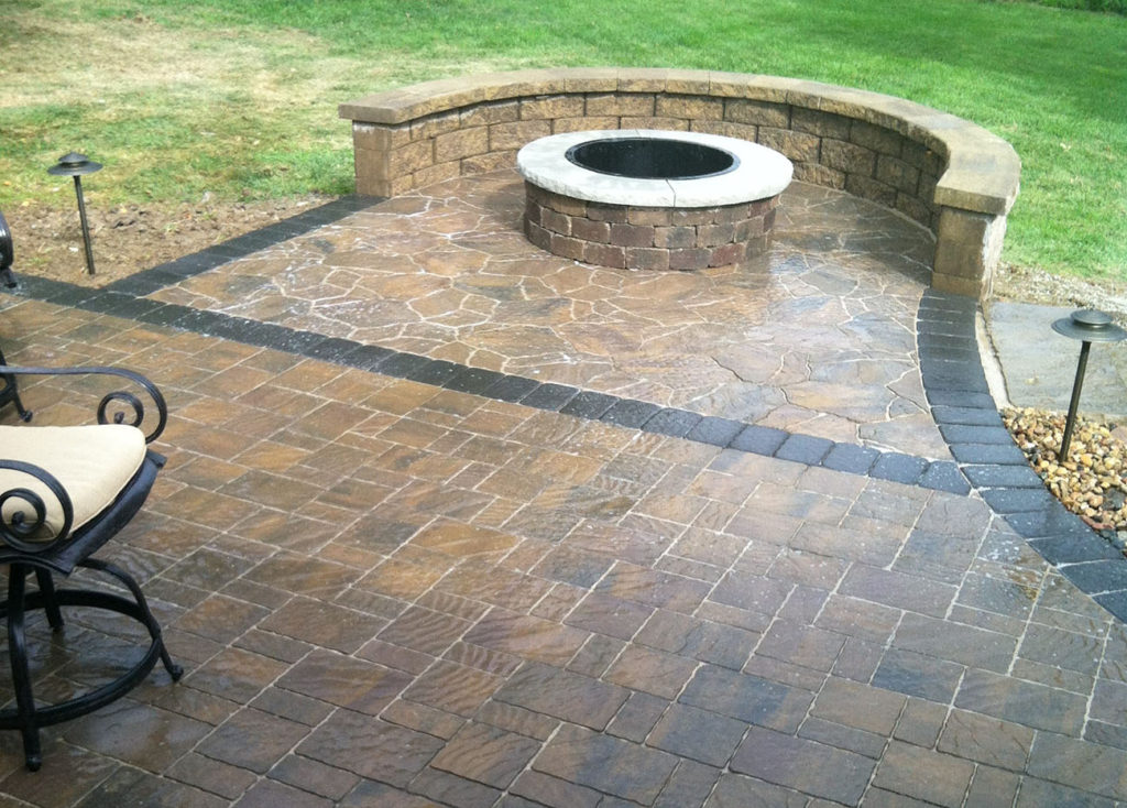 Round, stone fire pit with freestanding stone wall on patio with flagstone pavers
