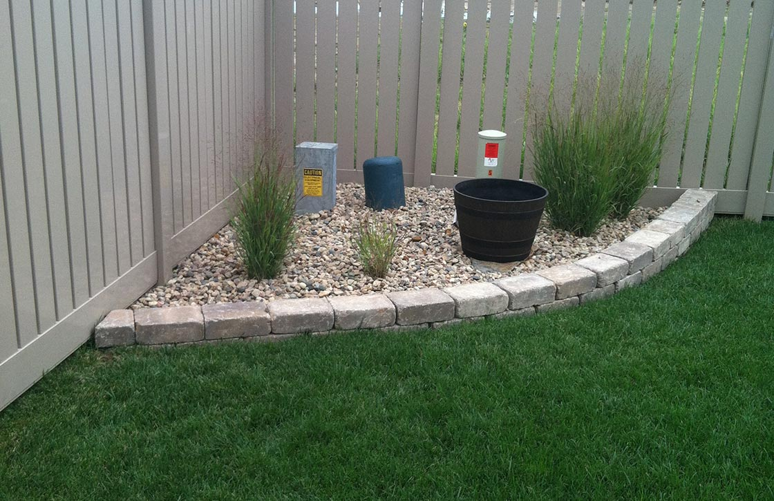 Landscape showcasing maintenance of raised corner berm along fence