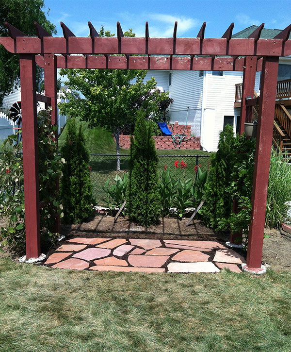 Pergola with decorative foliage and flagstone pavers