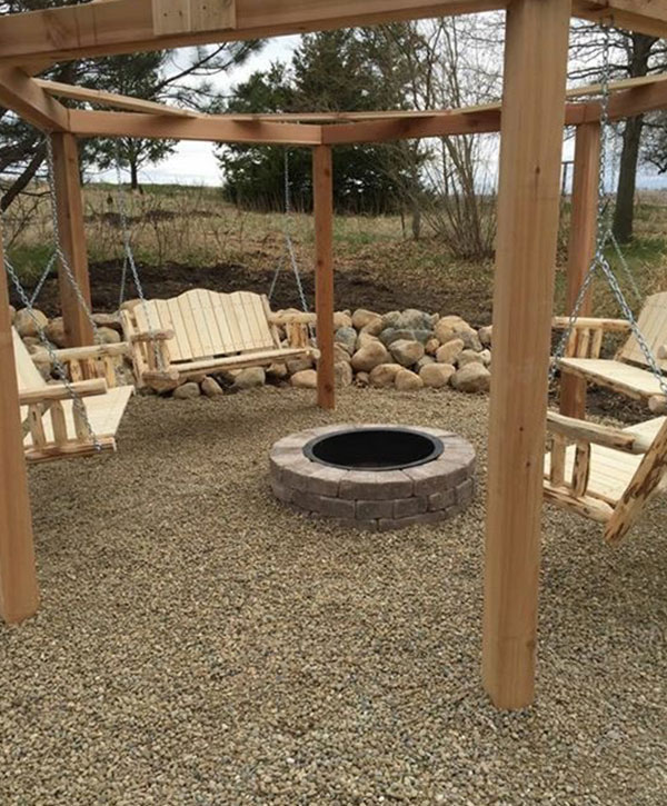 Specialty, custom built, circular pergola with wooden swings and raised fire pit